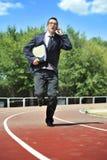 Affärsman i bärande mappportfölj för dräkt och för slips och mappar som kör i spänning på idrotts- spår som talar på mobiltelefon Arkivbilder