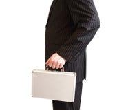 Affärsman i den svarta dräkten som rymmer en vit resväska Arkivfoto
