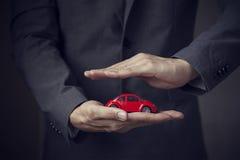 Affärsman i dräkt med två händer i positionen som skyddar en bil Arkivfoton