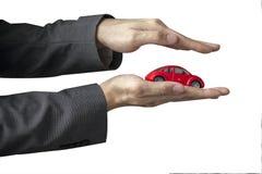 Affärsman i dräkt med två händer i positionen som skyddar en bil Arkivbild