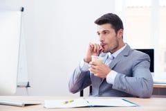 Affärsman i dräkt som dricker med is kaffe med sugrör royaltyfria foton