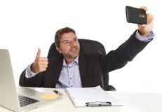 Affärsman i dräkten som arbetar på skrivbordet för kontorsbärbar datordator genom att använda mobiltelefonen för att ta selfiefot royaltyfria foton