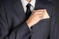 Affärsman i dräkten som sätter sedlar i hans omslagsbröstfack fotografering för bildbyråer