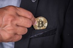 Affärsman i dräkthackabitcoin in som ska stoppa i fickan Royaltyfri Bild