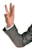 Affärsman i dräktshower tre fingrar Arkivbild