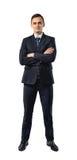 Affärsman i eleganta svarta ställningar för en dräkt med vikta armar som isoleras på en vit bakgrund Royaltyfri Bild