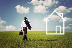 Affärsman i en dräkt som går till huset till en rymlig gräsplan f Arkivfoto