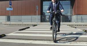 Affärsman i en dräkt som rider en cykel till och med en övergångsställe i tid hans morgonlopp till jobbet stock video