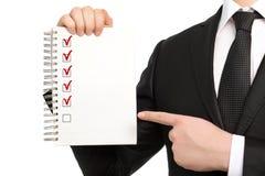 Affärsman i en dräkt som rymmer en anteckningsbok eller ett stycke av papper Arkivfoto