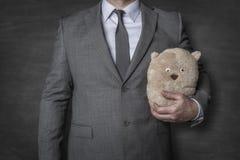 Affärsman i en dräkt som rymmer en nallebjörn royaltyfria foton