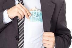 Affärsman i en dräkt som sätter pengar i hans fack Arkivfoto
