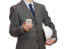 Affärsman i en grå dräkt med en telefon i hans hand och med ett p Arkivfoto