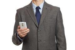 Affärsman i en grå dräkt med en telefon i hans hand och med ett p Arkivfoton