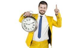 Affärsman i en guld- dräkt som rymmer en klocka i hans händer Arkivbilder