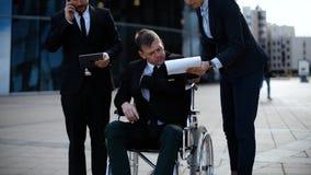 Affärsman i en rullstol med kollegor utanför en kontorsbyggnad stock video