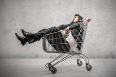Affärsman in i en shoppingvagn fotografering för bildbyråer
