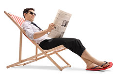 Affärsman i en solstol som läser en tidning Royaltyfria Bilder