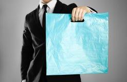 Affärsman i en svart dräkt som rymmer en blå plastpåse close upp Isolerad bakgrund arkivfoto