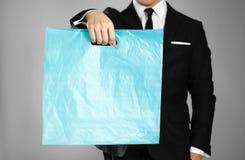 Affärsman i en svart dräkt som rymmer en blå plastpåse close upp Isolerad bakgrund arkivbilder