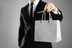 Affärsman i en svart dräkt som rymmer en grå pappers- gåvapåse close upp Isolerad bakgrund royaltyfri fotografi