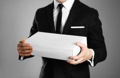 Affärsman i en svart dräkt som rymmer en vit ask close upp Isolerad bakgrund royaltyfri foto