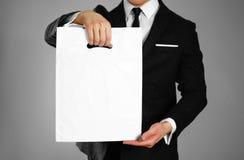 Affärsman i en svart dräkt som rymmer en vit plastpåse close upp Isolerad bakgrund royaltyfri fotografi