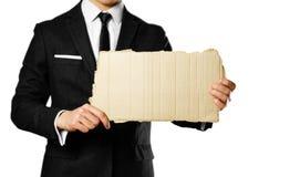 Affärsman i en svart dräkt, en vit skjorta och ett band som rymmer ett stycke arkivbild