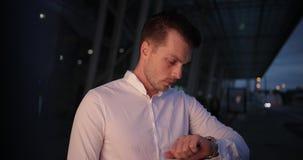 Affärsman i en tur Den upptagna unga stiliga mannen ser runt om och på hans armwatch som utanför väntar på en taxi stock video