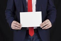 Affärsman i ett omslag som rymmer ett tomt ark i hans hand, affärsman royaltyfri fotografi