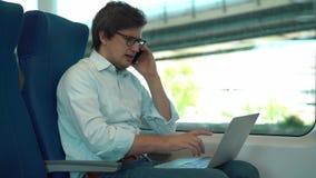 Affärsman i exponeringsglas som talar på telefonen och använder bärbara datorn i ett drev stock video