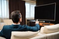 Affärsman i formellt dräktsammanträde på soffan i hotellrum royaltyfria foton