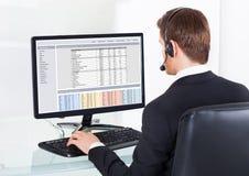 Affärsman i hörlurar med mikrofon genom att använda datoren på skrivbordet Royaltyfri Fotografi
