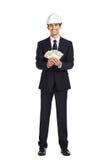 Affärsman i hjälmhandpengar royaltyfri foto