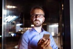 Affärsman i kontoret på natten som sent arbetar Fotografering för Bildbyråer