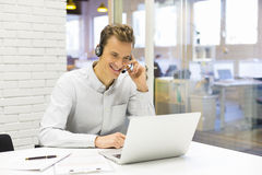 Affärsman i kontoret på telefonen med hörlurar med mikrofon, Skype Royaltyfri Foto