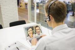 Affärsman i kontoret på videokonferens med hörlurar med mikrofon, Skype Arkivfoton