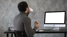 Affärsman i kontoret som har frukosten, lunch och håller ögonen på något på macen, dator Vit skärm royaltyfri bild