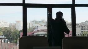 Affärsman i kontur som talar på telefonen stock video
