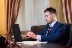 Affärsman i regeringsställning med bärbara datorn Fotografering för Bildbyråer