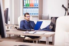 Affärsman i regeringsställning med hans fot på tabellen Arkivbild
