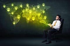 Affärsman i regeringsställning med minnestavlan och den sociala nätverksvärldskartan Arkivbild