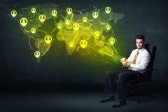 Affärsman i regeringsställning med minnestavlan och den sociala nätverksvärldskartan Arkivfoton