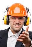 Affärsman i säkerhetshardhathjälm som gör en gest handhälsning eller Arkivfoto