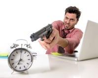 Affärsman i spänning på skrivbordet för kontorsdator som in pekar handvapnet till ringklockan ut ur att förfalla för tid- och pro Royaltyfri Foto