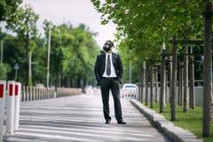 Affärsman i staden som bär en gasmask royaltyfri bild