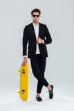 Affärsman i sunglaasses som lutar på skateboarden med korsade ben Arkivfoton