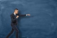 Affärsman i svart dräktanseende som, om han ska stansa något som är osynlig nära den blåa svart tavlan Arkivfoto