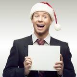 Affärsman i tecken för santa hattholding Fotografering för Bildbyråer