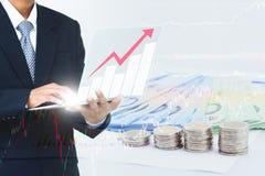 Affärsman i vinst för hållande övervakning för dräkt finansiell med sedlar och mynt i bakgrund Arkivfoton