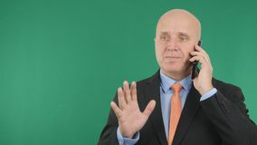 Affärsman Image som använder mobiltelefonen som ler och gör en gest royaltyfri foto